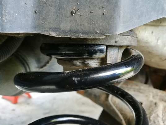 This is how the coil spring should be seated in the upper mount – up against the stop.